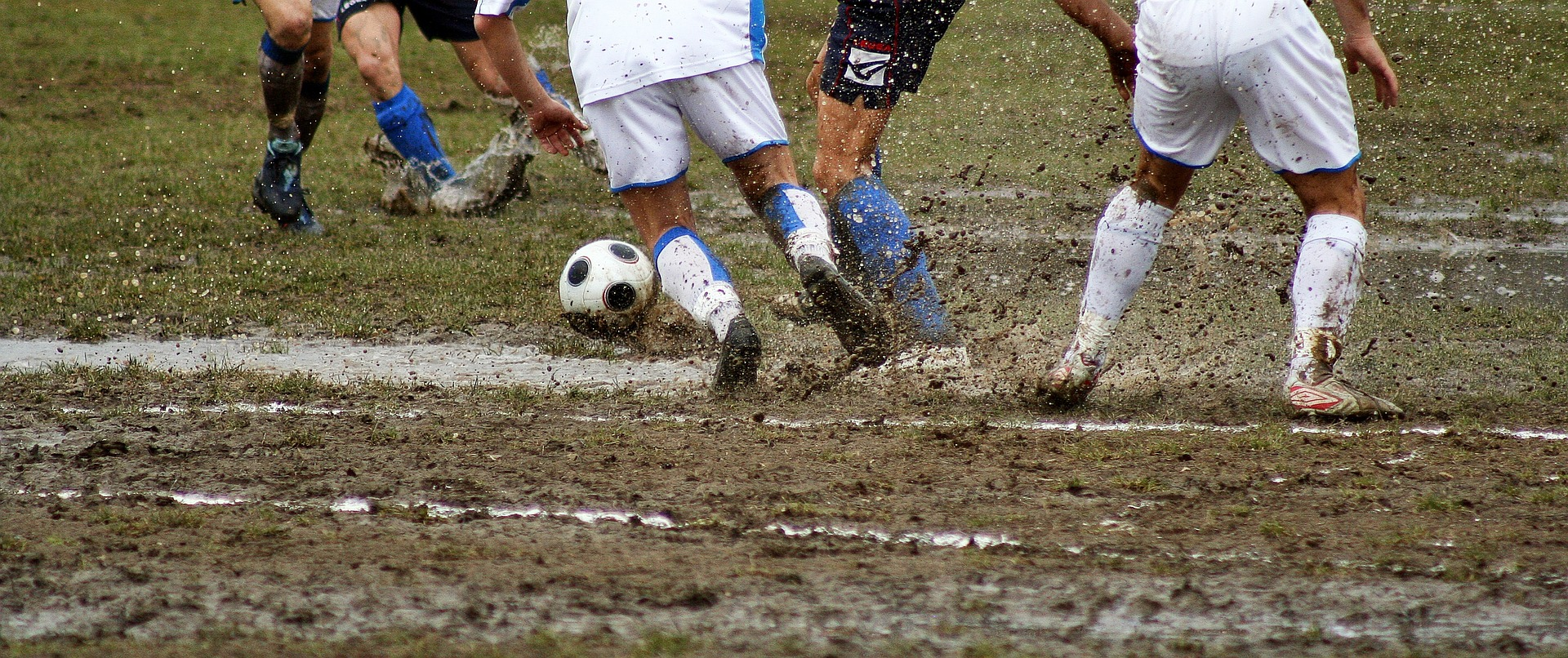 Fußballspieler im Matsch mit Adidas Europass OMB